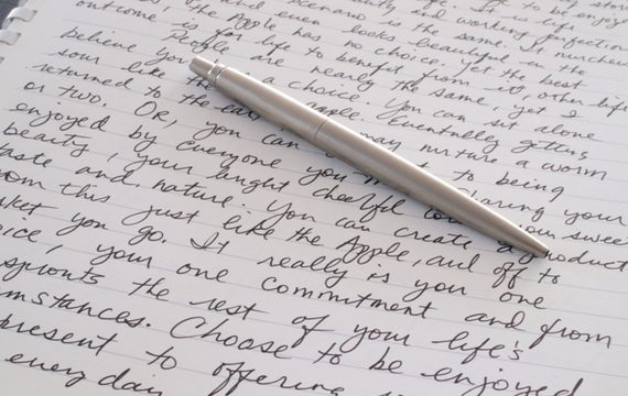 A Stainless Steel Ball Point Pen is Laying on the Written Page of a Spiral Bound Notebook